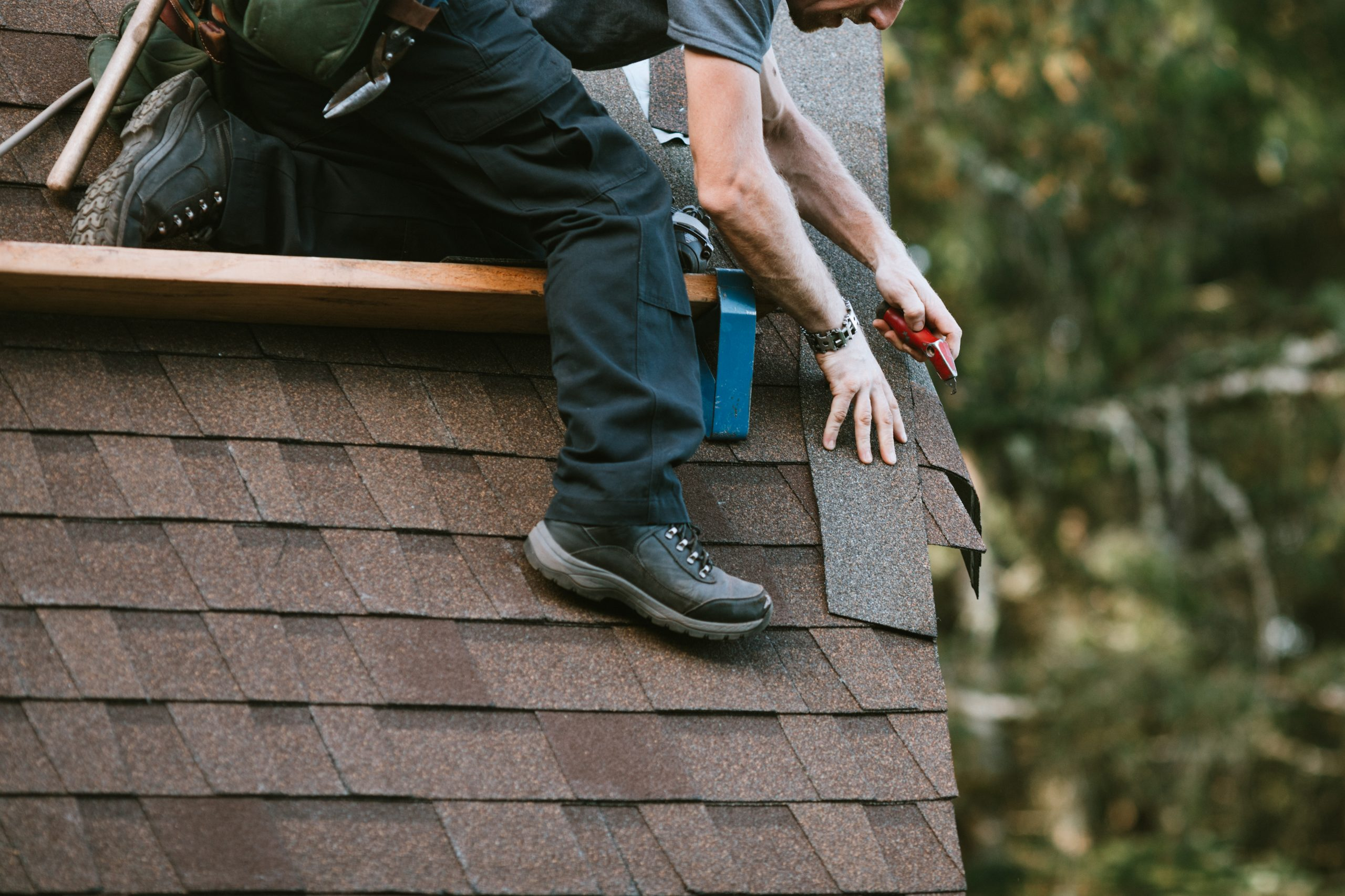 A roofer and crew work on putting in new roofing shingles.  Small local business serving local families in Washington State.